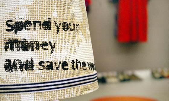 En lampa med texten: Spend your money and save the world.