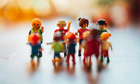 Close up photo of a handful Playmobil human figures in different colors and sizes.