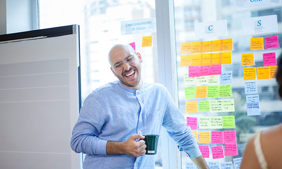 Cover photo: Caio with tons of post-its during a serving design workshop at work.